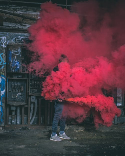 Photo of Man Surrounded by Red Smoke
