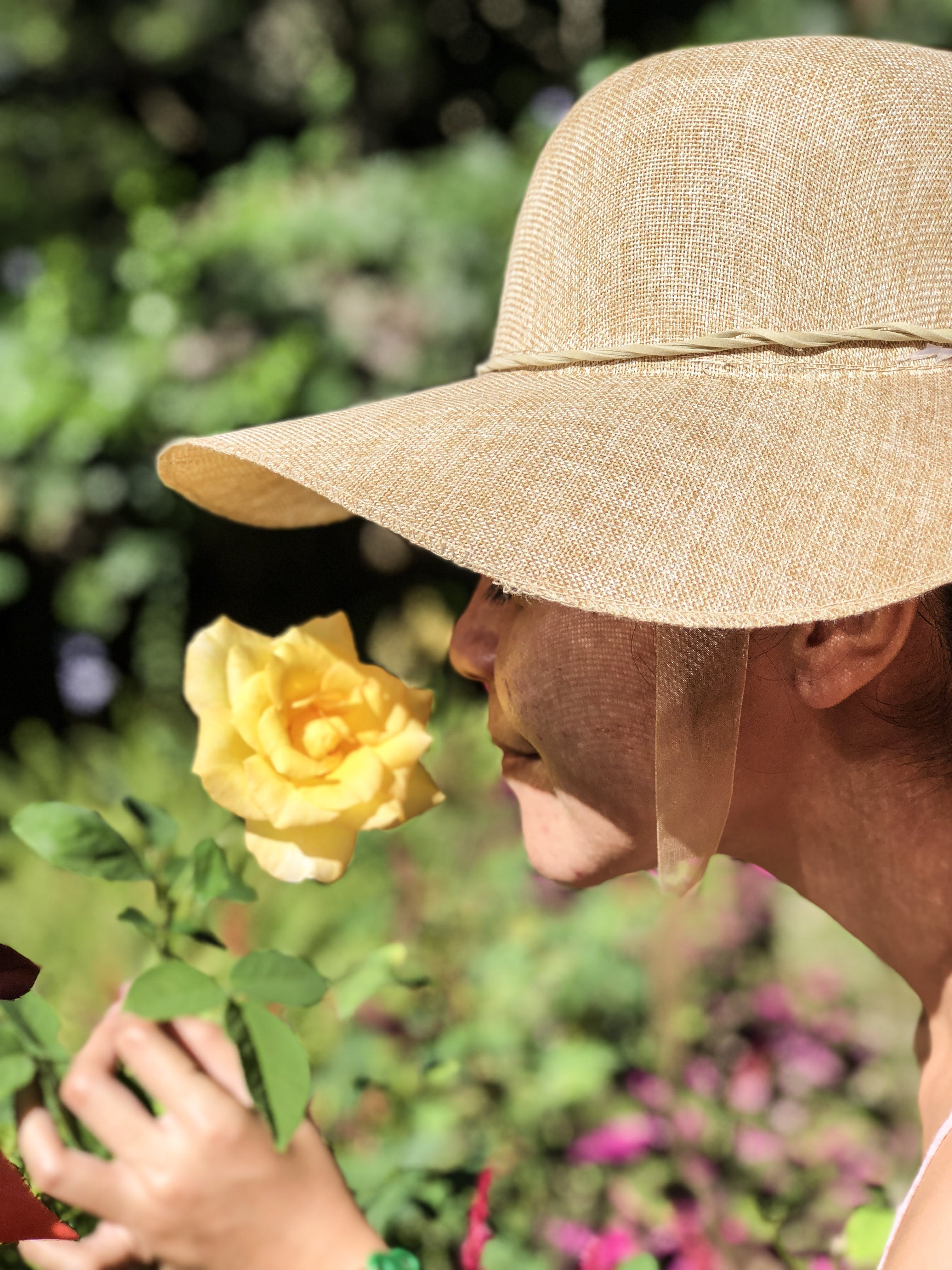 Woman Wearing Sun Hat Smelling Yellow Rose