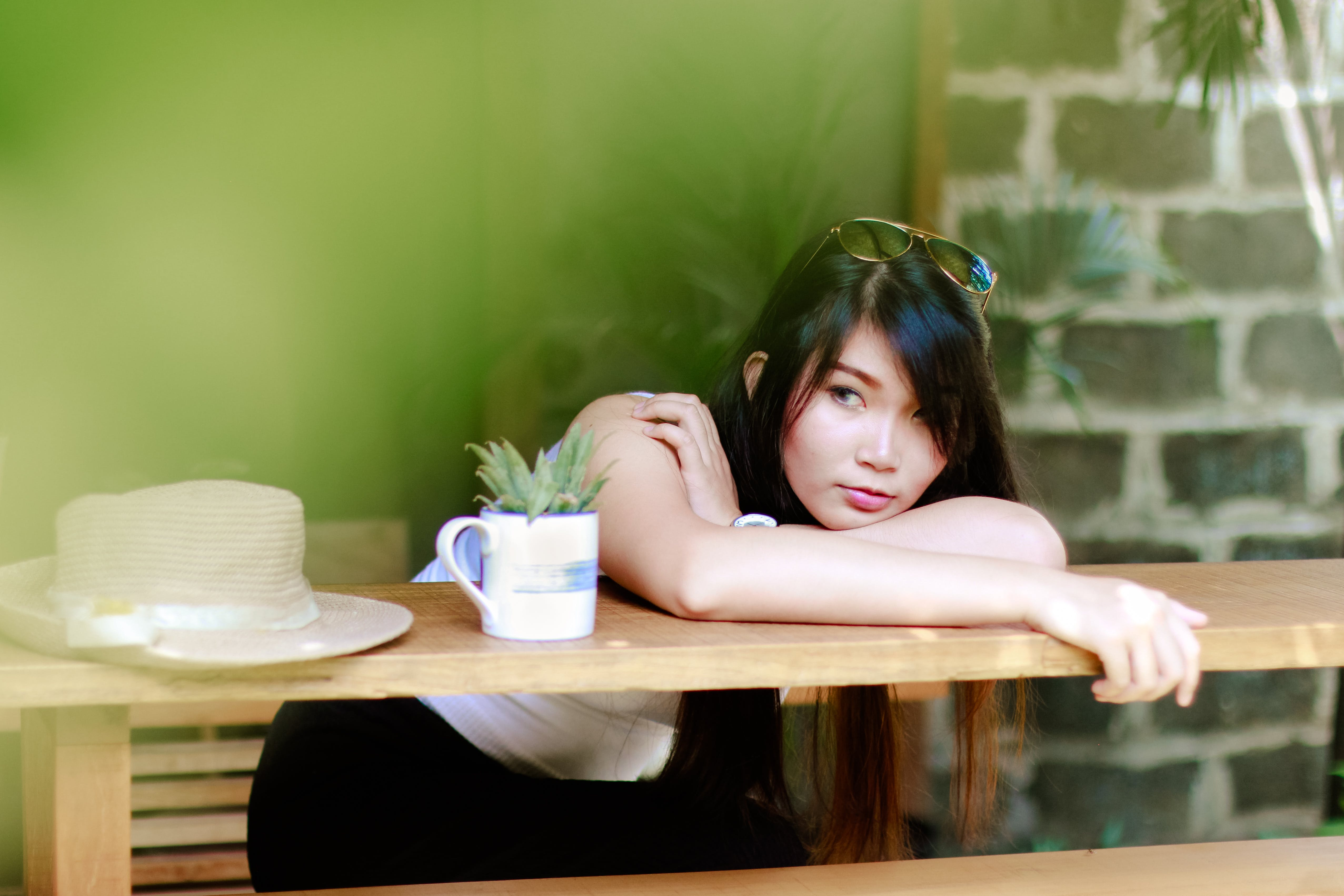 Woman Wearing White Shirt Sitting Near Table