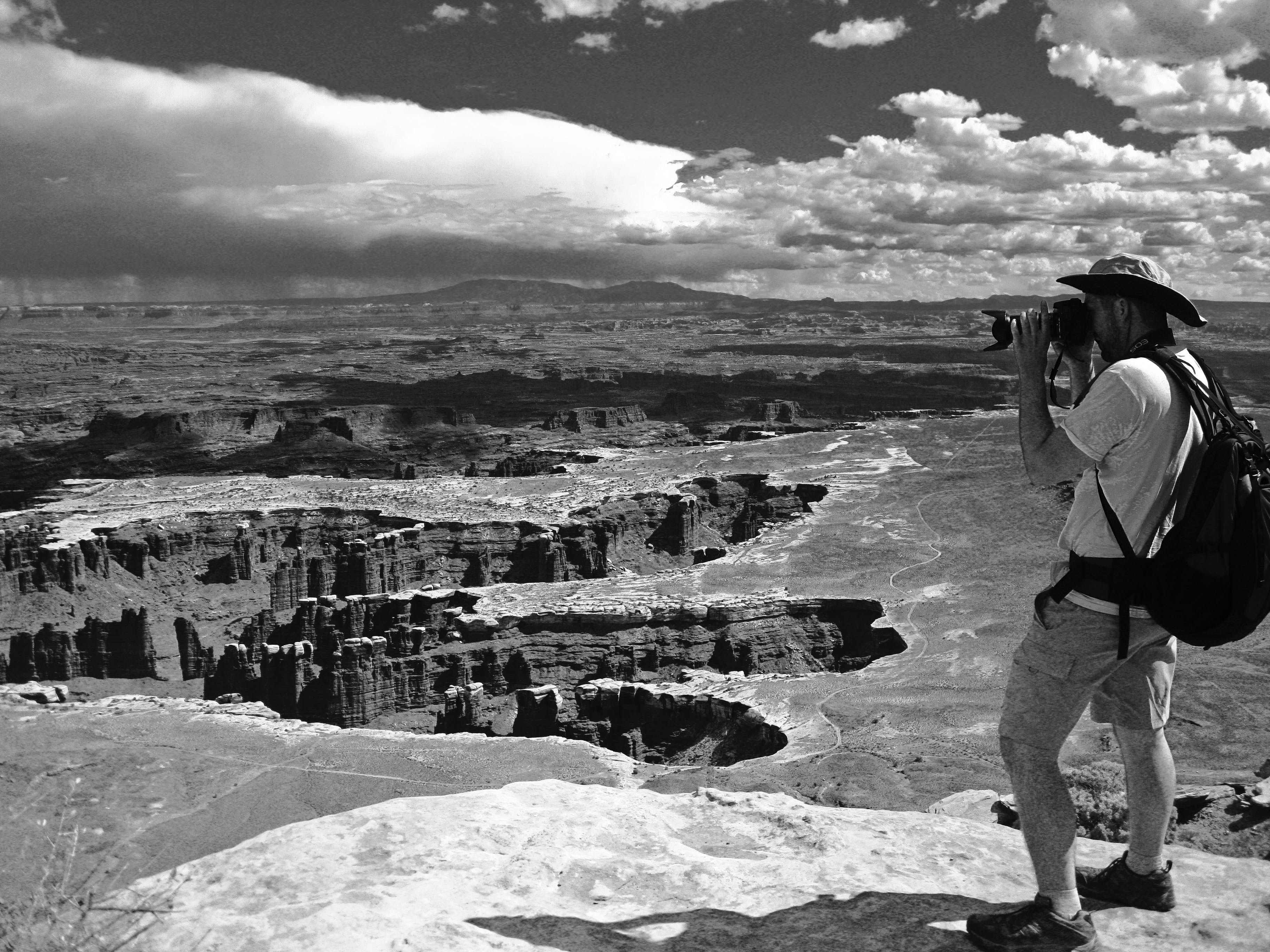 Grayscale Photo of Man Taking Photo of Canyons
