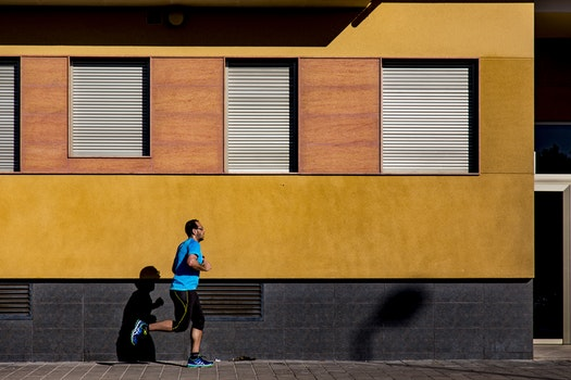 Jogging Man Wearing Blue Shirt during Daytime