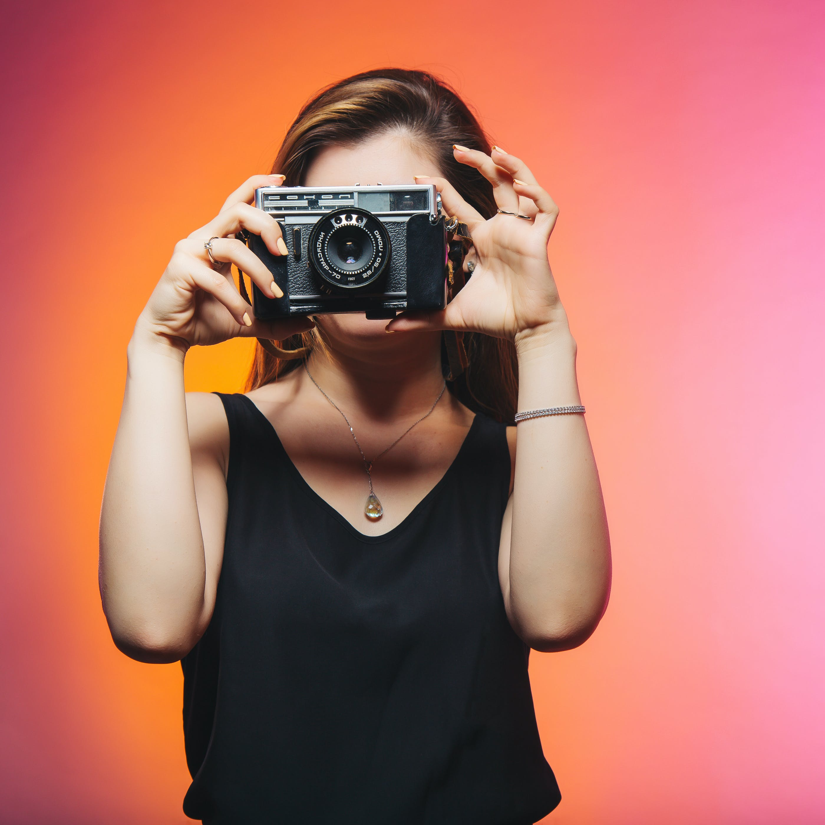 Woman Wearing Black Sleeveless Top Holding Gray Camera