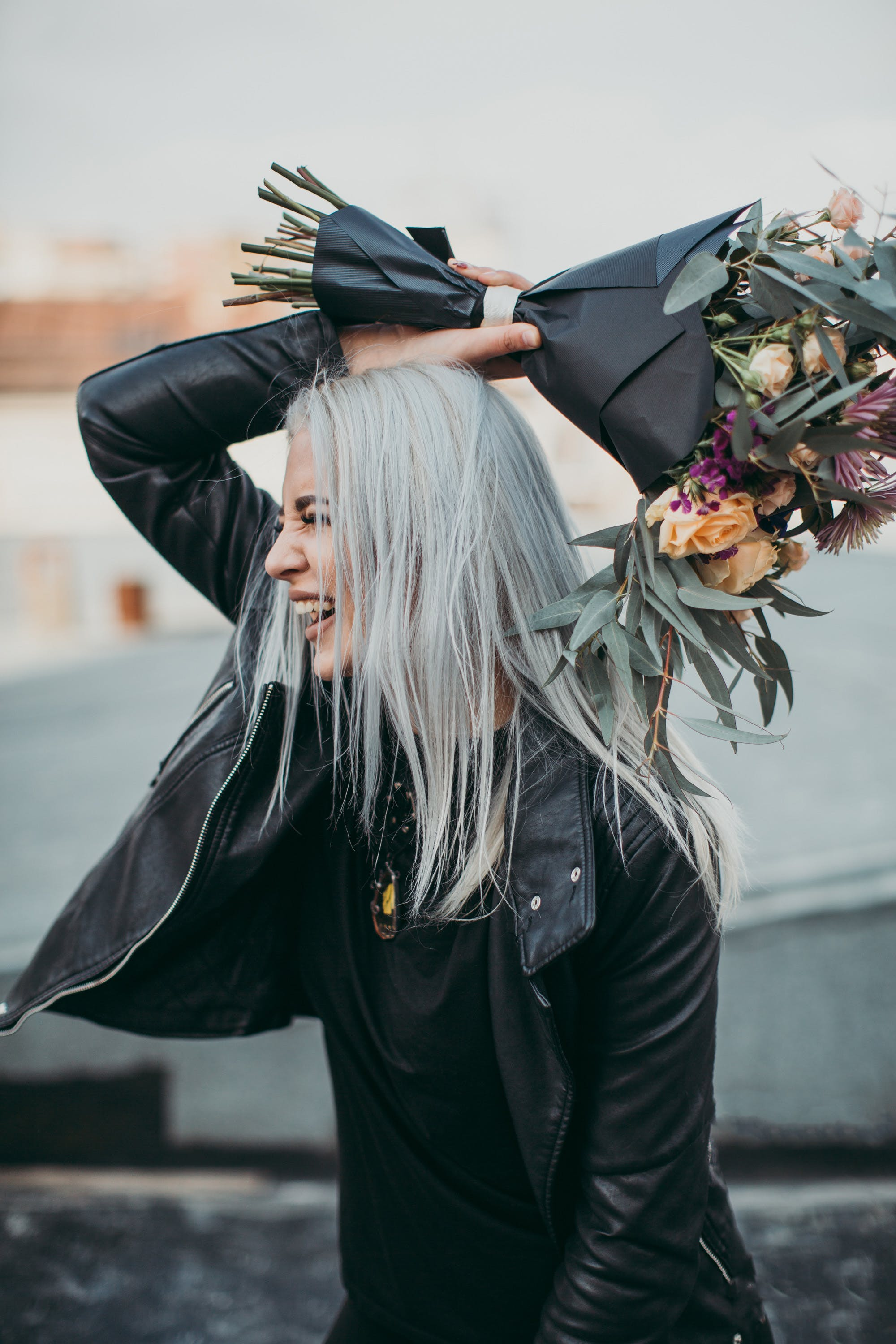 Woman Wearing Black Leather Jacket Holding Flower Bouquet