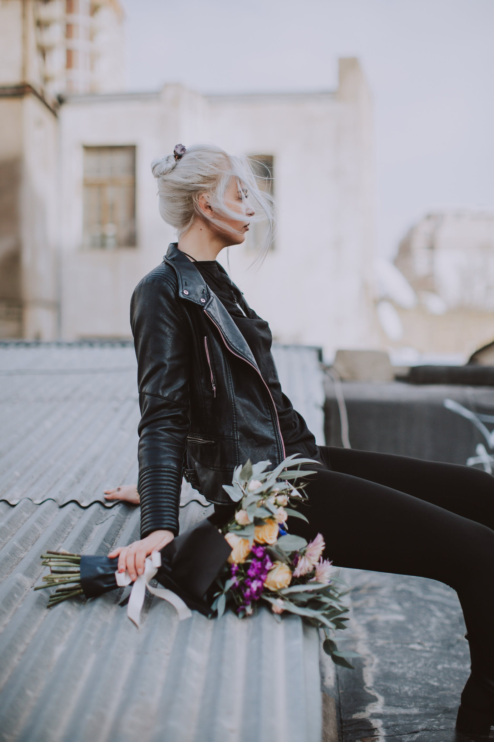 Woman Wearing Black Leather Full-zip Jacket Sitting on Galvanized Roof