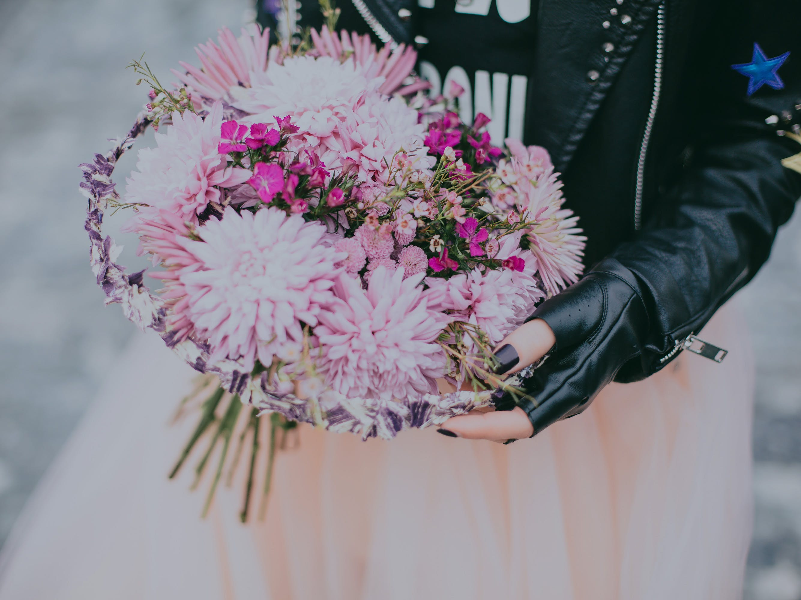 Person in Black Leather Jacket Pink and Red Flower Bouquet