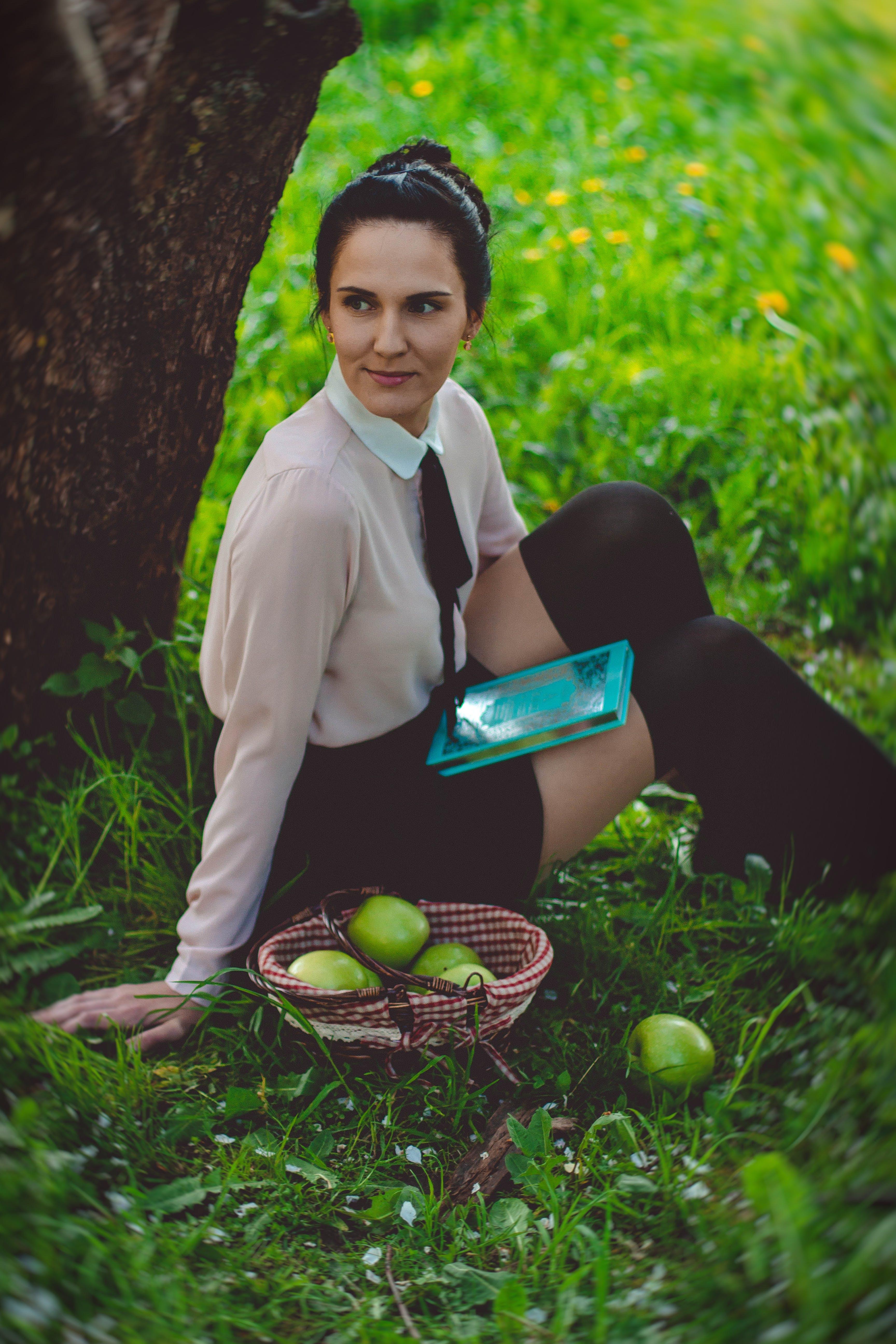 Woman Weasring White Dress Shirt Sitting in Green Grass Under Brown Large Tree