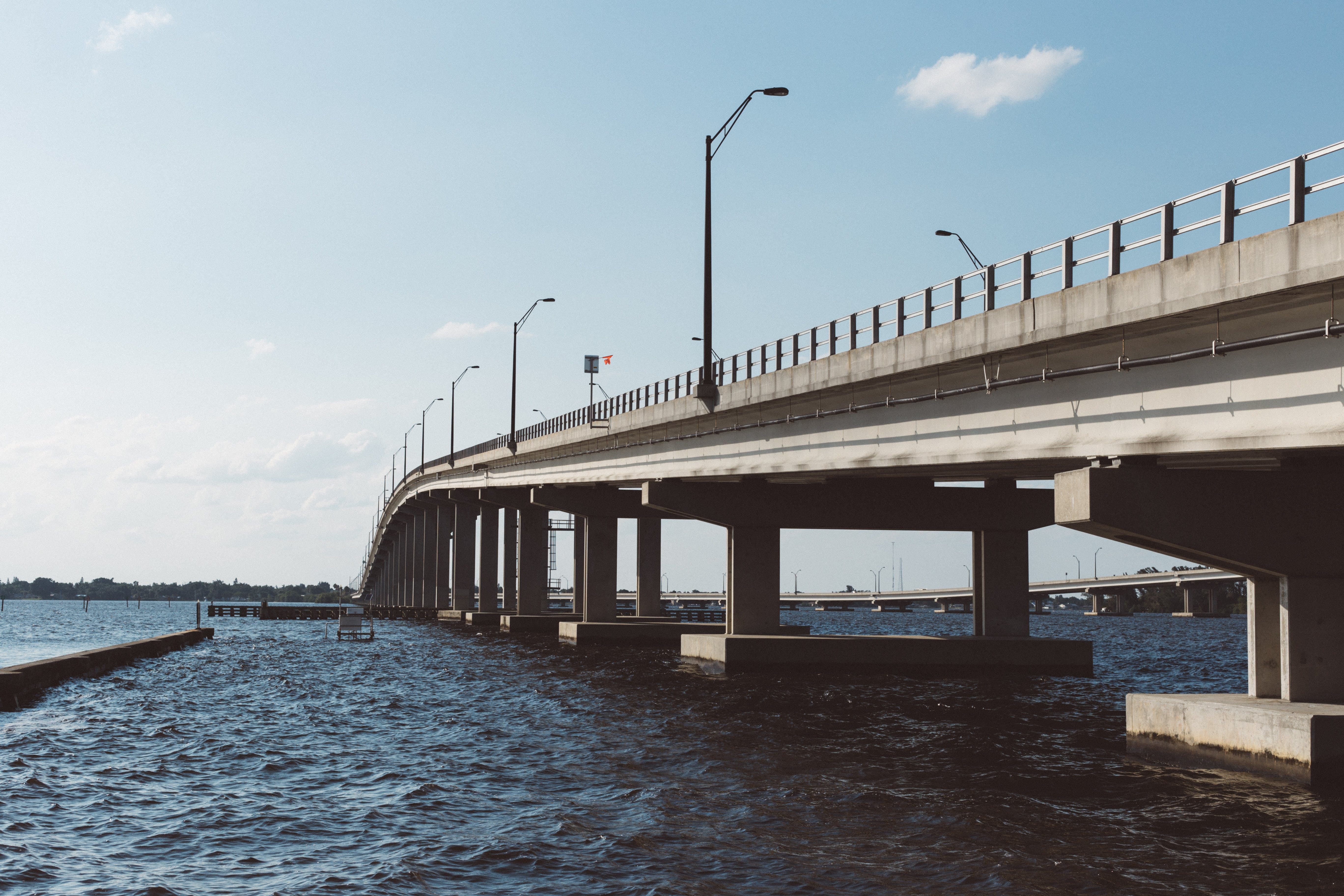 Brown Concrete Bridge Above Body of Water Under Blue Sky and White Clouds