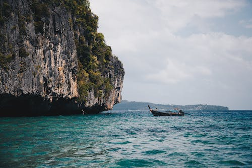 Boat Beside Cave on Body of Water