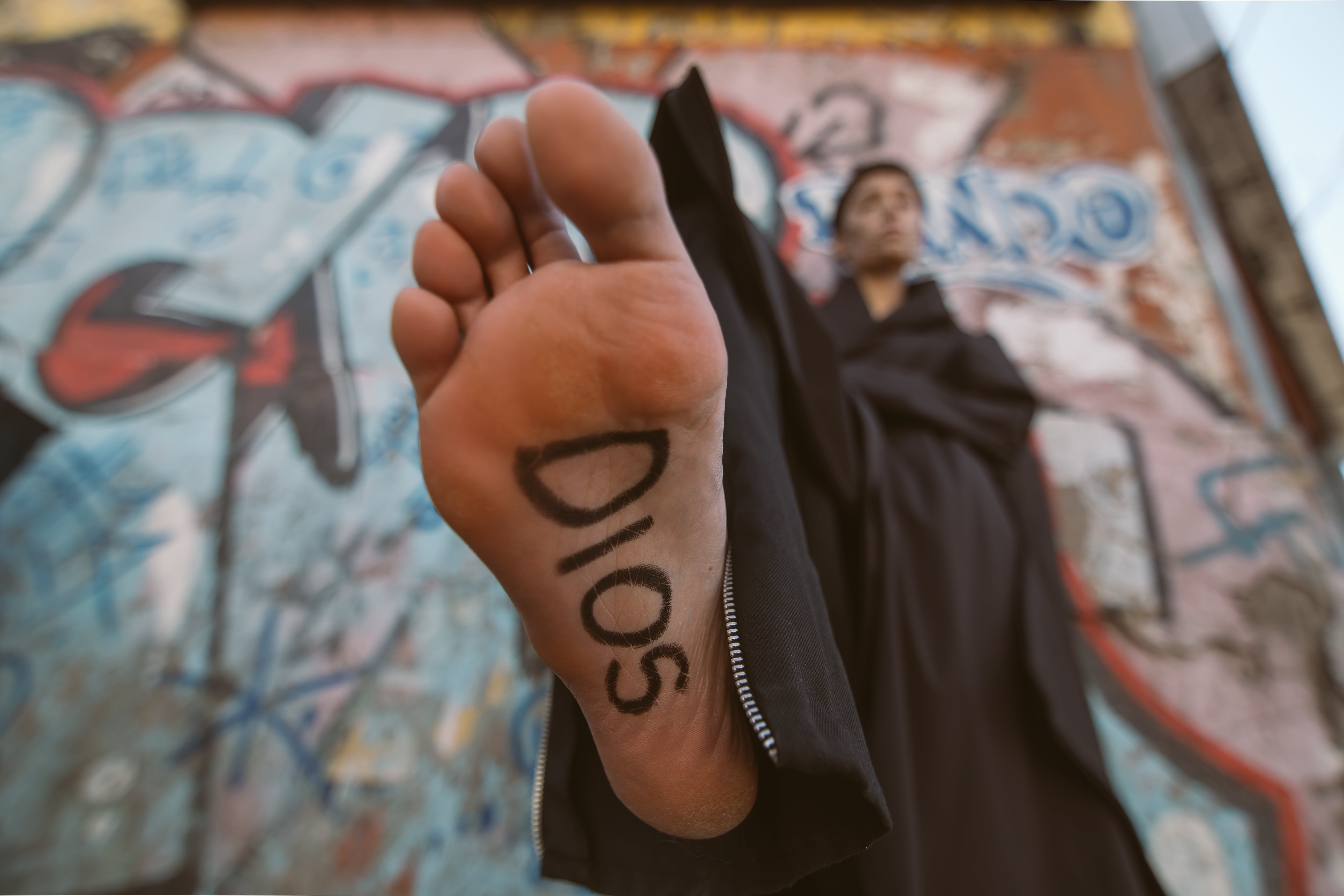 Person Wearing Black Robe With Sign on Foot