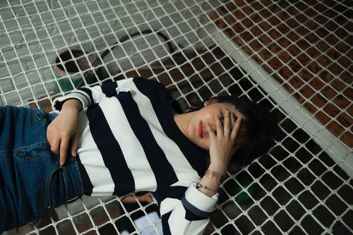 Woman in Black and White Striped Long-sleeved Top Lying on Black Net