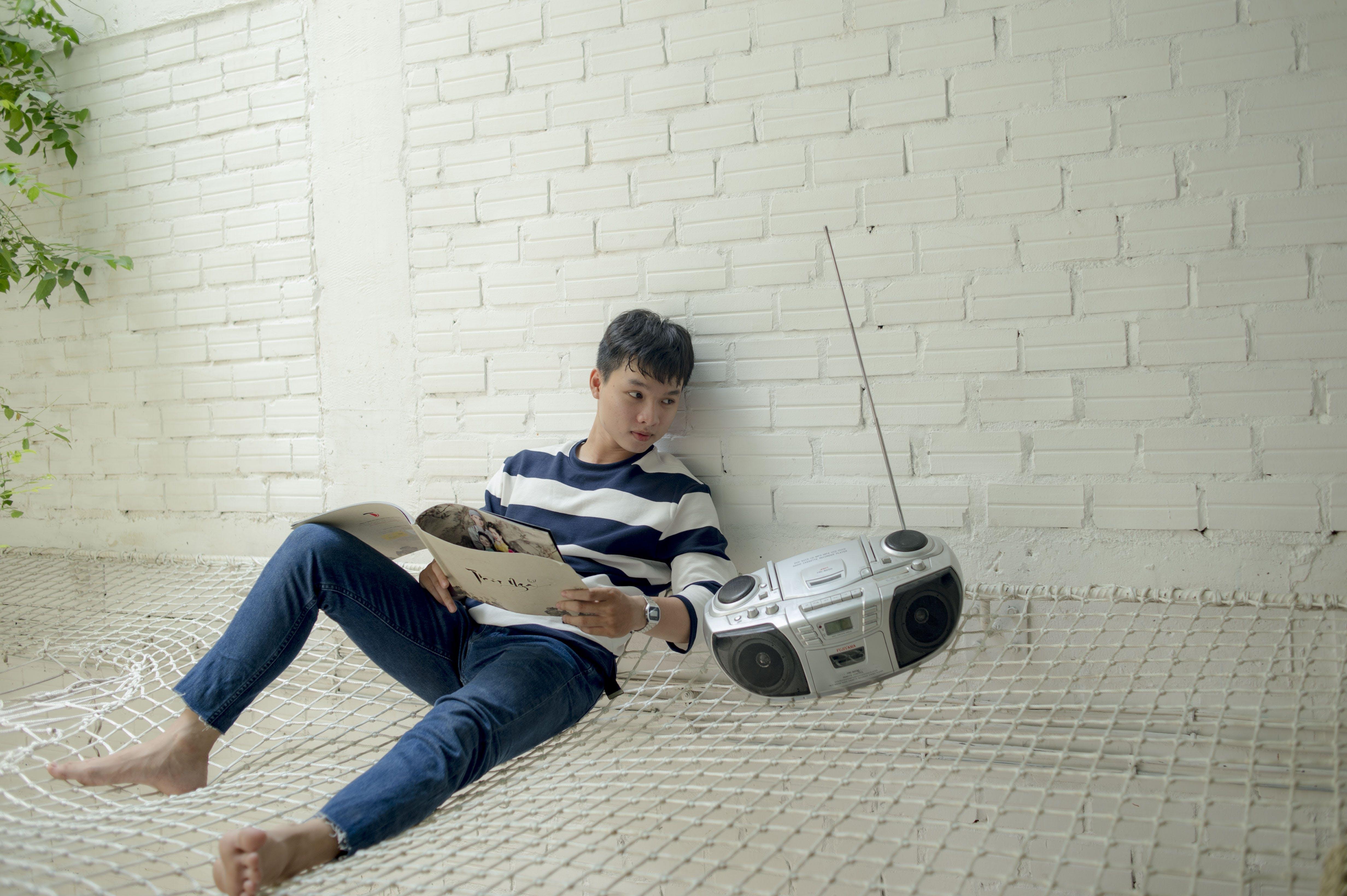 Boy Sitting Near Radio Holding White Catalog