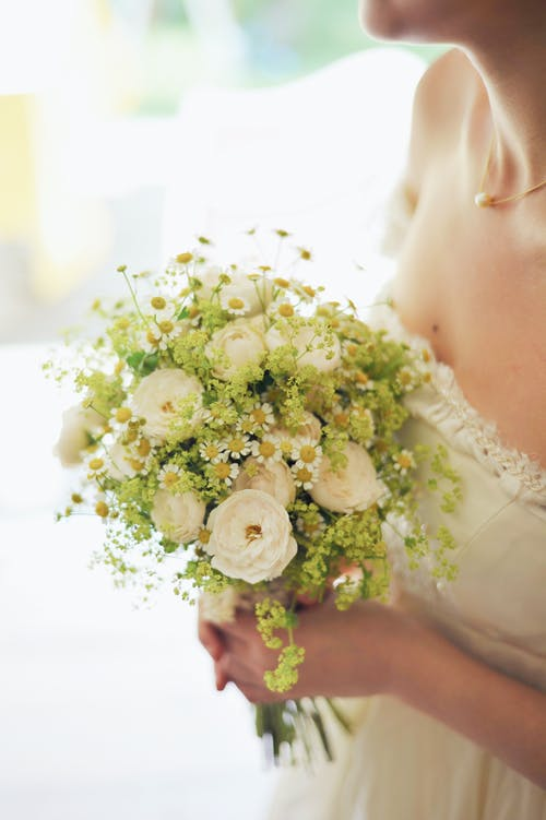 Woman in Bridal Gown Holding Bouquet of White Flowers