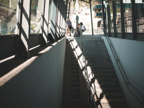 People Sitting on Bench Near Staircase