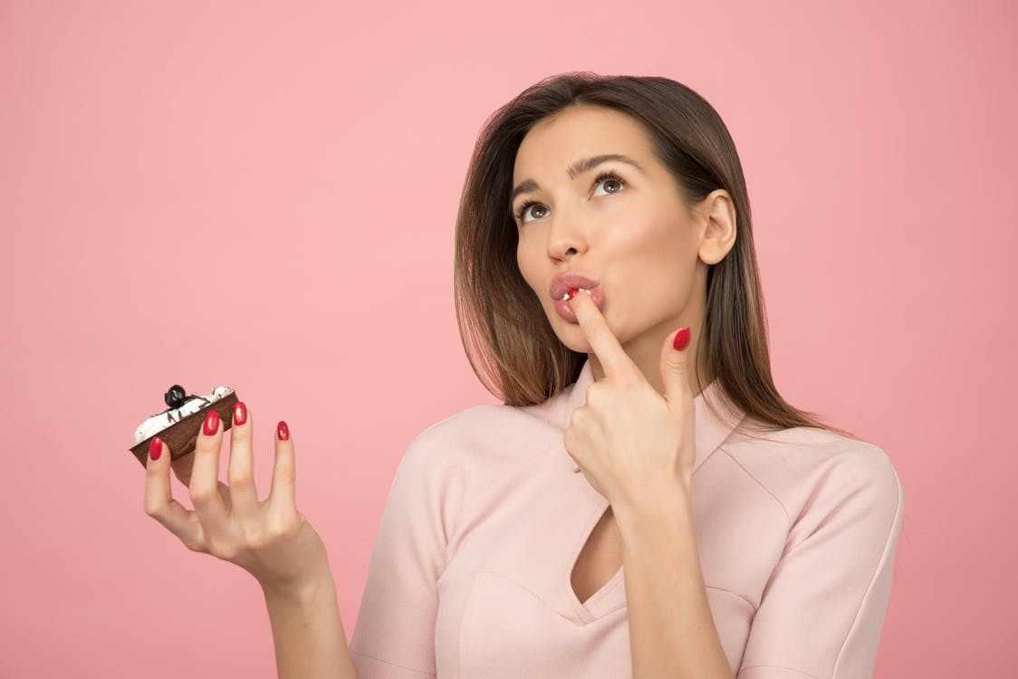 Woman Eating Cupcake While Standing Near Pink Background Inside Room