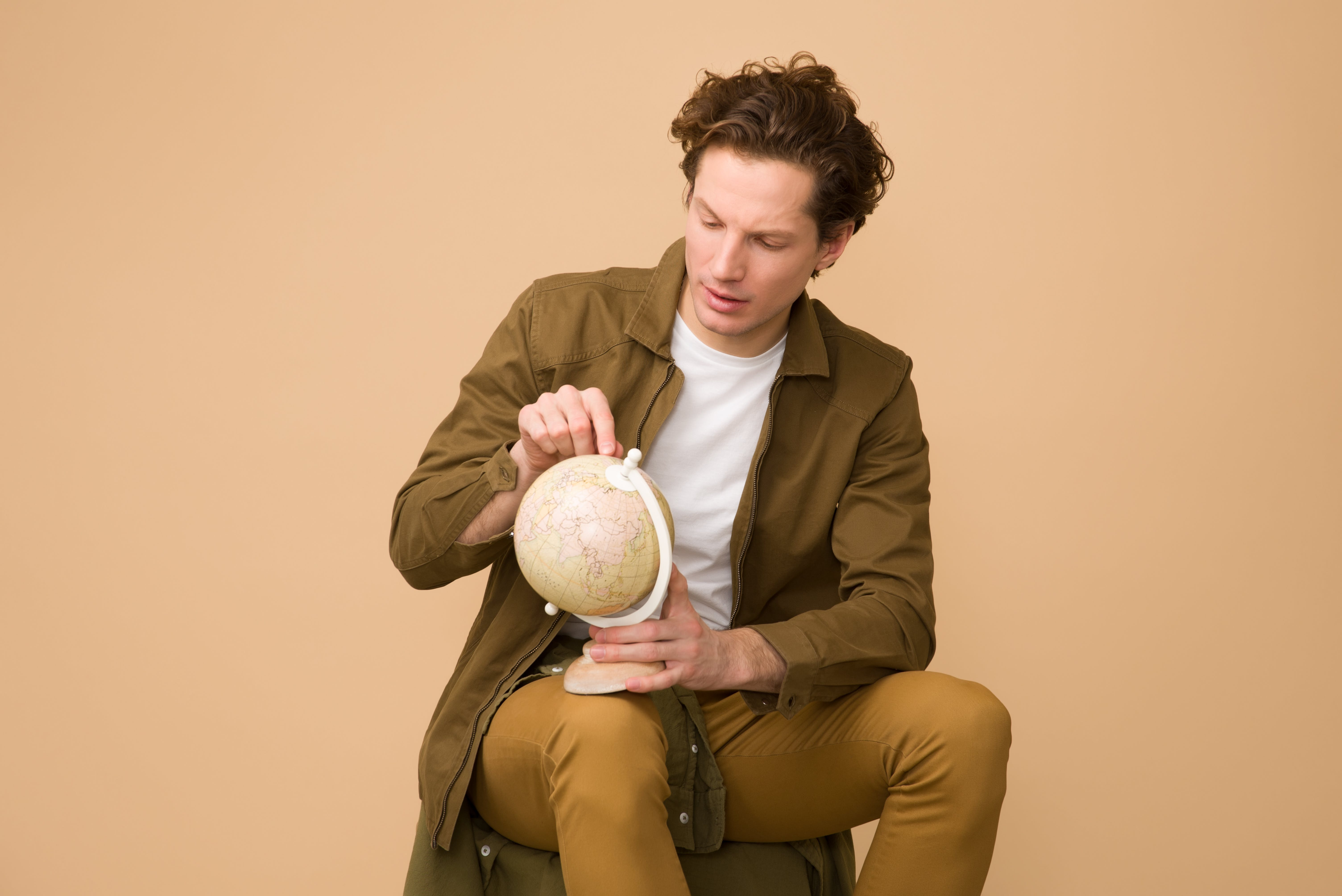 Man Sitting Holding White Desk Globe