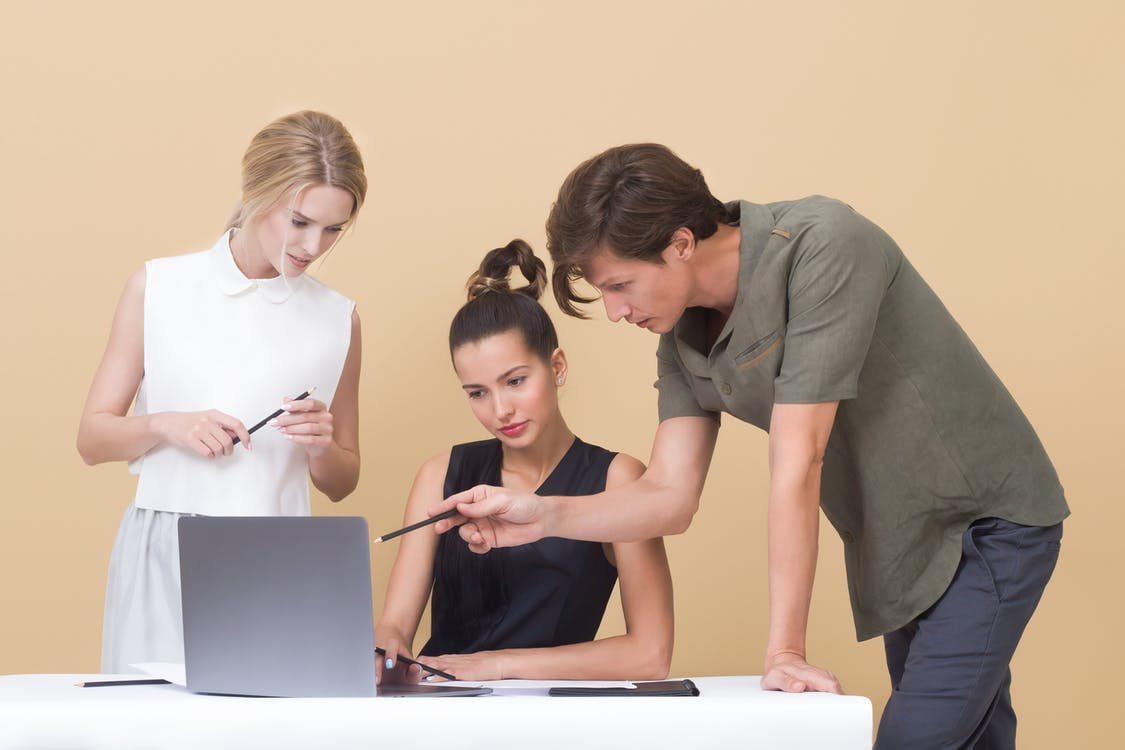 Two Woman and One Man Looking at the Laptop