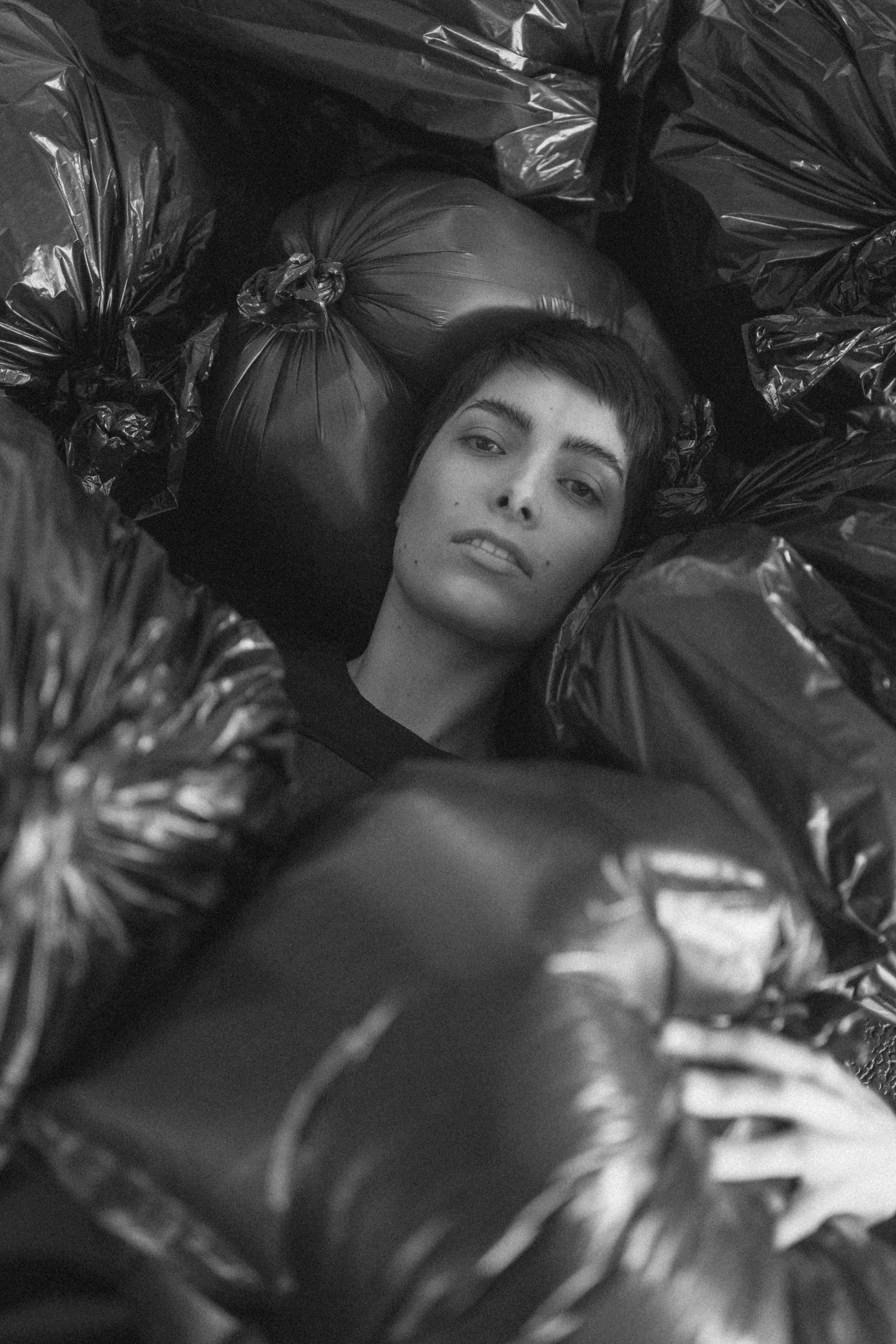 Grayscale Photo of Female Surrounded by Black Plastic Bags