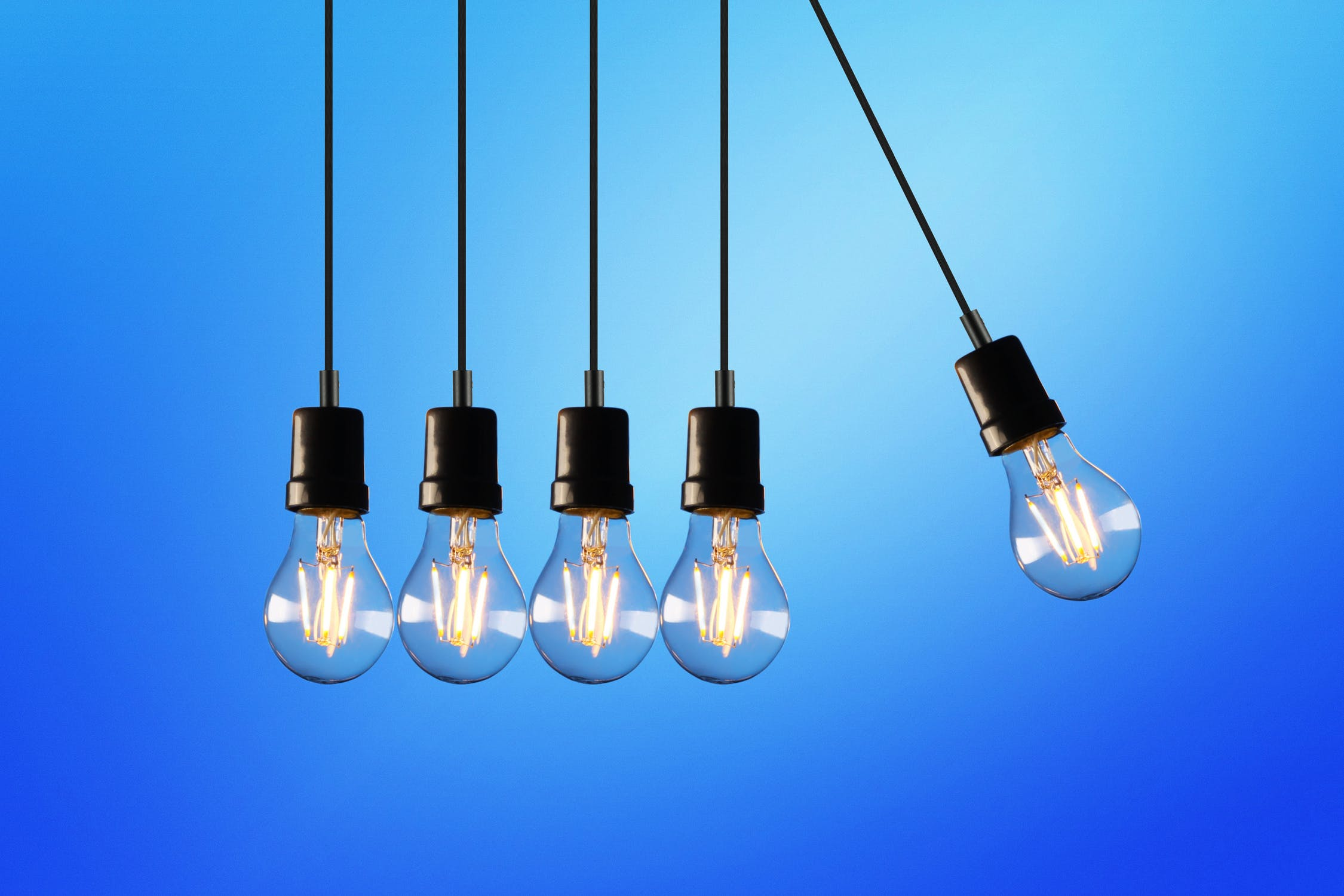 Five incandescent bulbs hanging and swinging like newton's cradle. Photo by pexels user Rodolfo Clix. Used courtesy of pexels.com