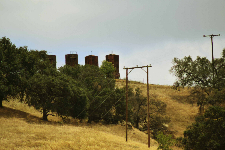 Gratis lagerfoto af grå himmel, højspændingsledning, silo, tørt græs