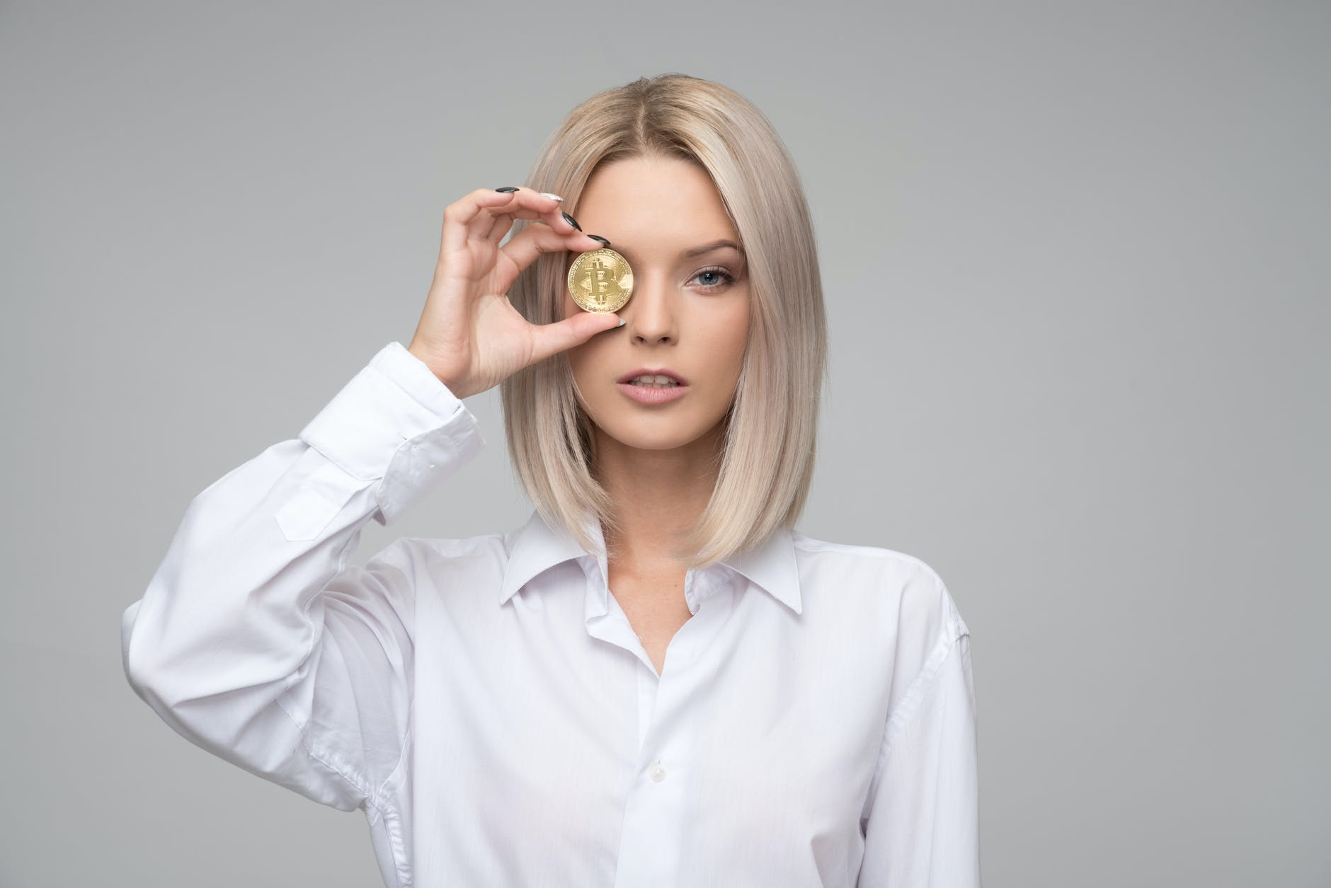 Woman holding a bitcoin on her eye