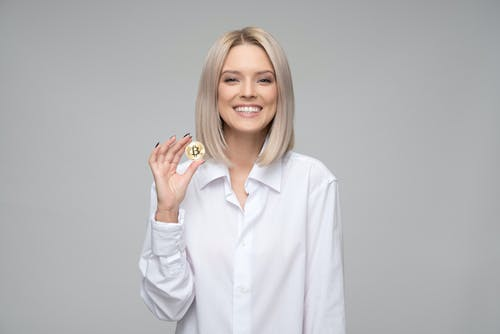 Women Wearing White Long-sleeved Collared Shirt Holding Bitcoin