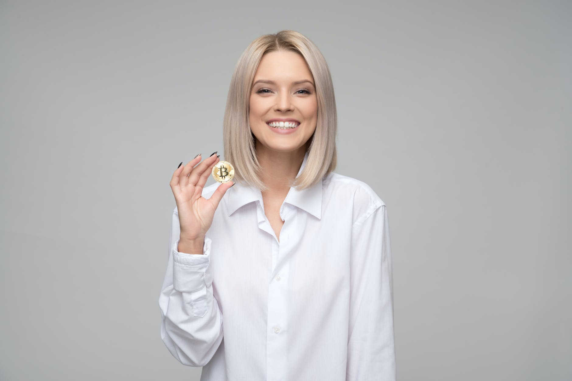 Woman wearing white shirt holding a bitcoin
