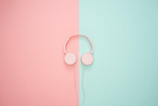 Pink Corded Headphones On And Teal Wall