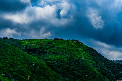 Landscape Photography of Green Mountain Under Cloudy Sky