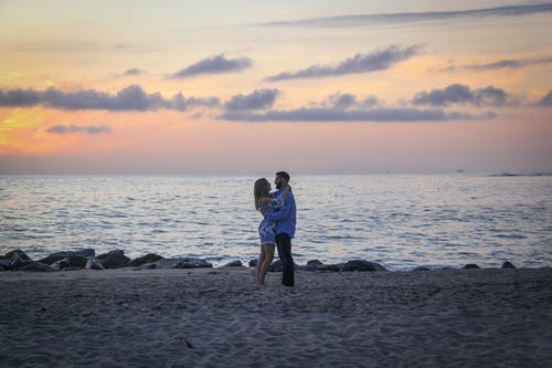 Couple Face to Face Stands on Seashore Near Calm Water during Golden Hour