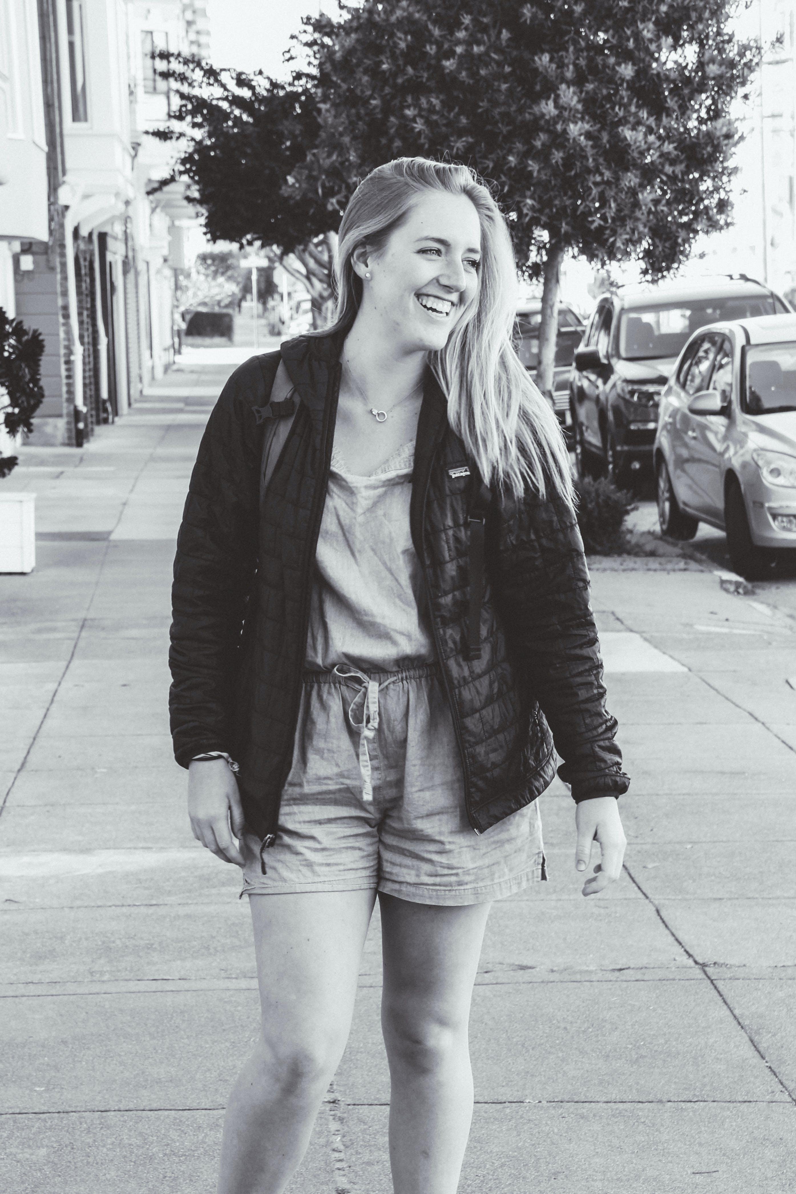 Greyscale Photo of Smiling Woman Wearing Jacket Standing on Pathway