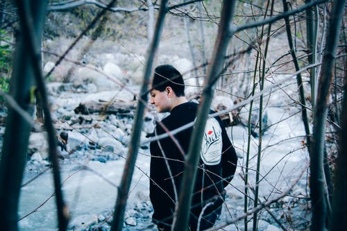 Man Wearing Black Sweatshirt Standing Beside River and Bare Trees