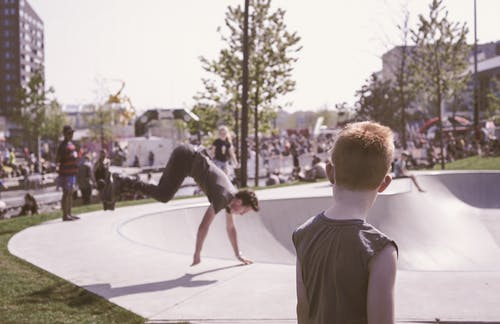 Man in Black Tank Top Looking at Man in Black T-shirt Doing Hand Stand Routine
