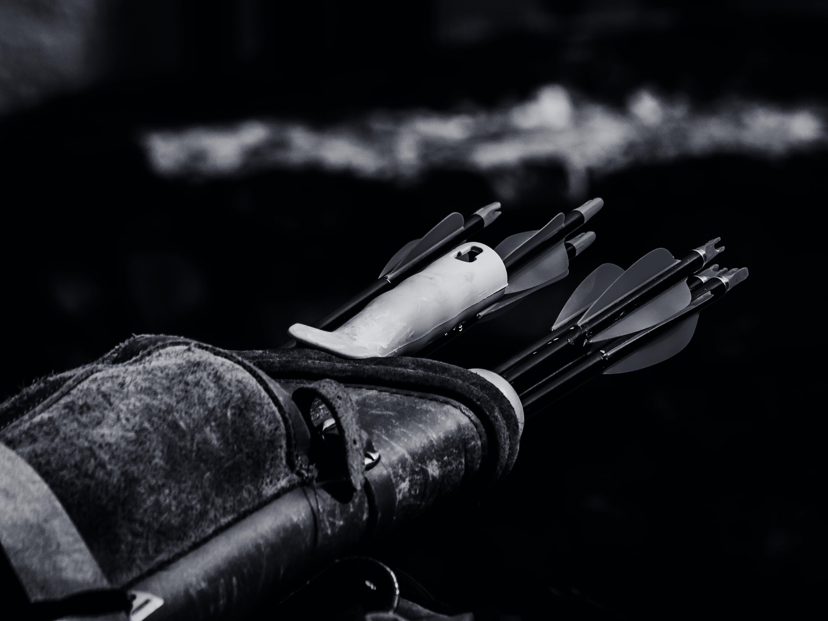 Grayscale Photo of Arrow Inside Black Case