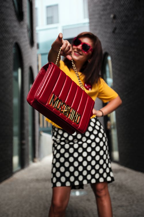 Woman Wearing Yellow Crew-neck T-shirt While Holding Red Handbag
