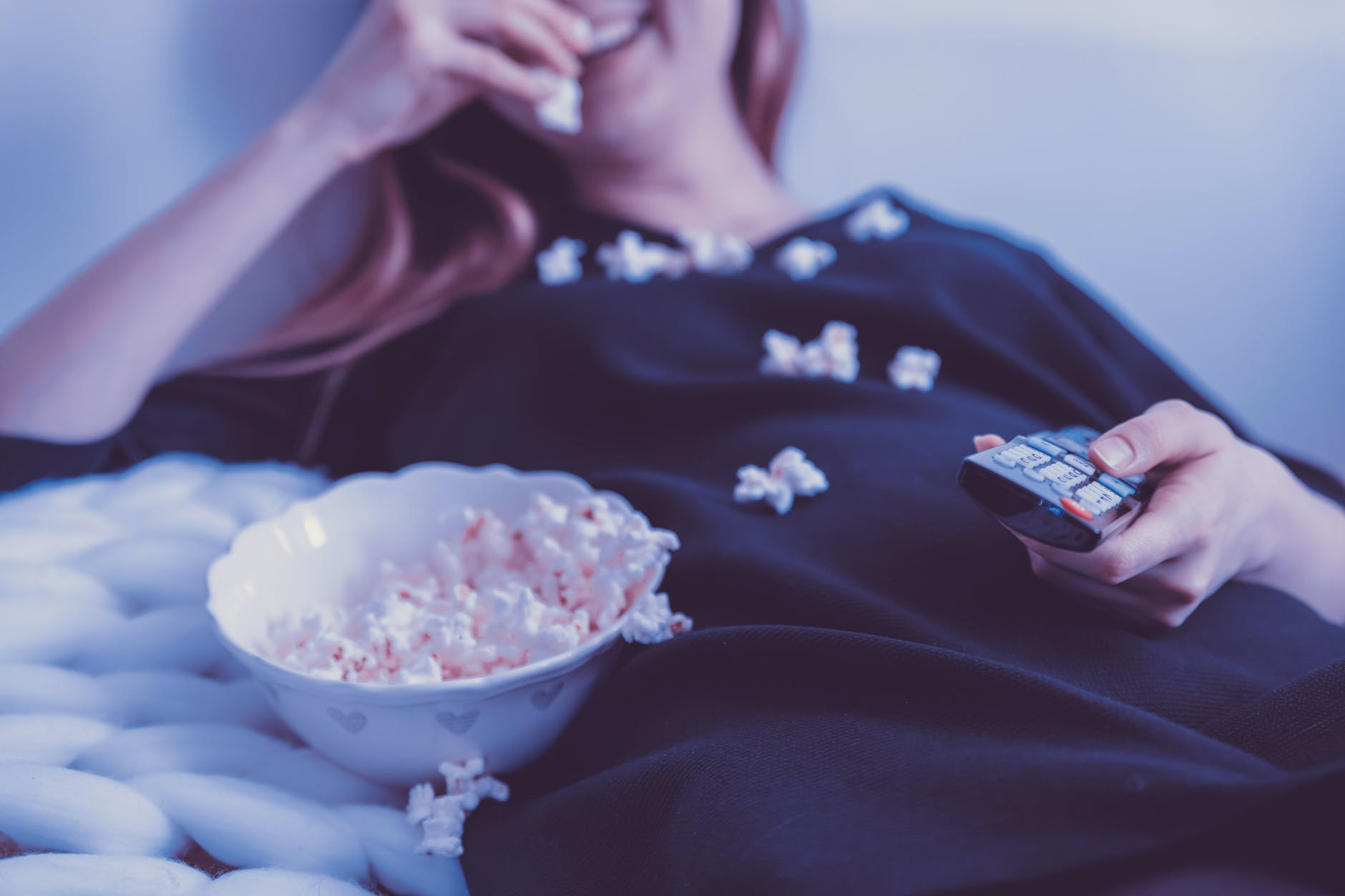 woman watching movies at home while eating popcorn