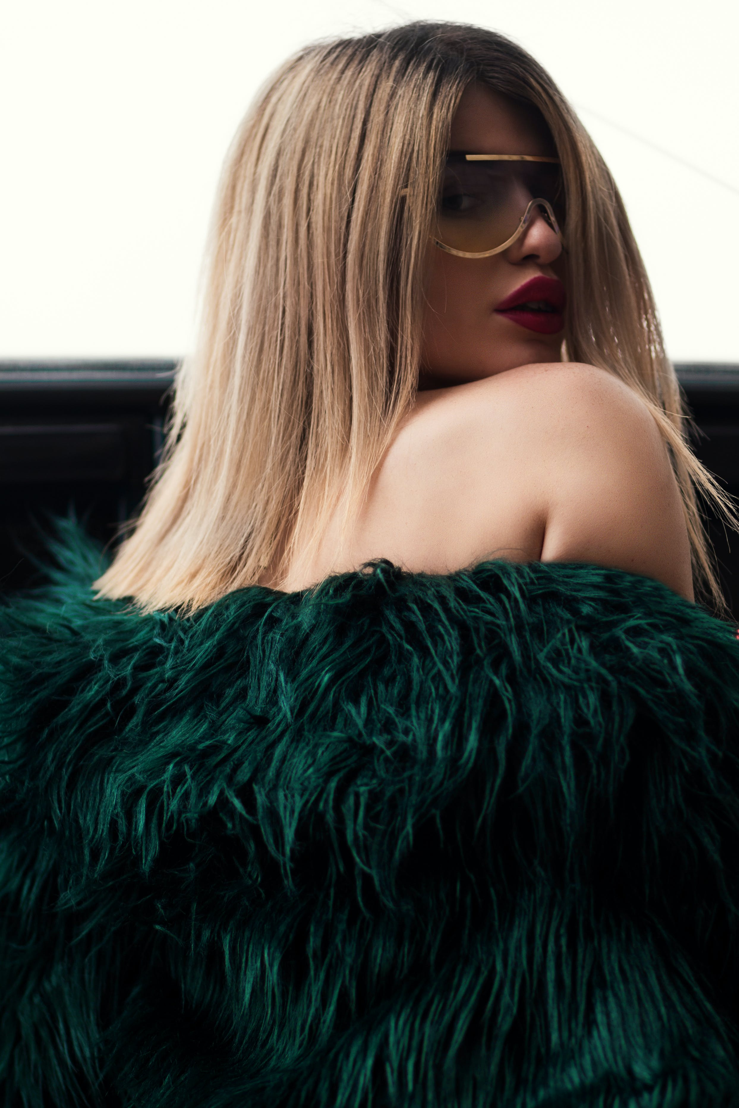 Woman in Green Fur Jacket Wearing Sunglasses With Gold Frame