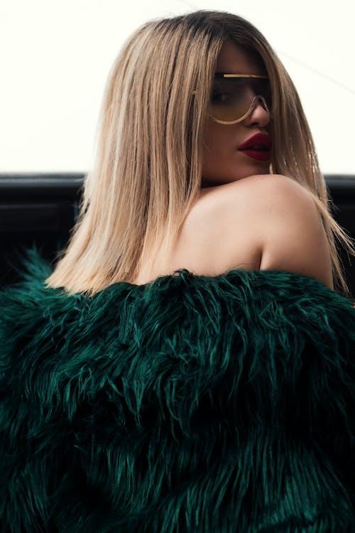 Женщина в зеленой шубе в солнцезащитных очках с золотой оправой
