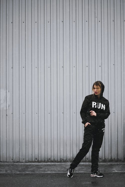 Woman in Black Hoodie, Pants, and Sneakers