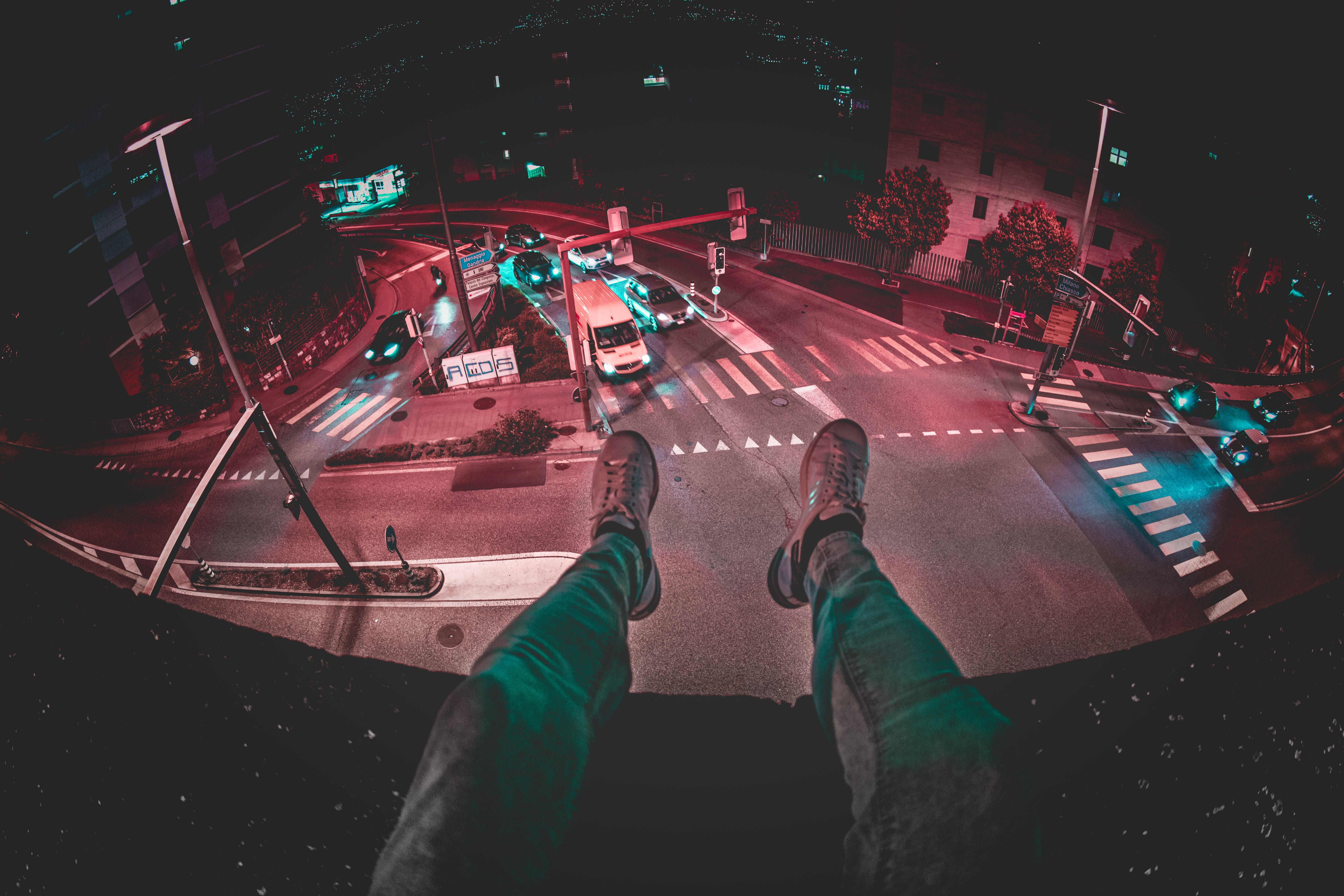 Person Sits on Building during Nighttime