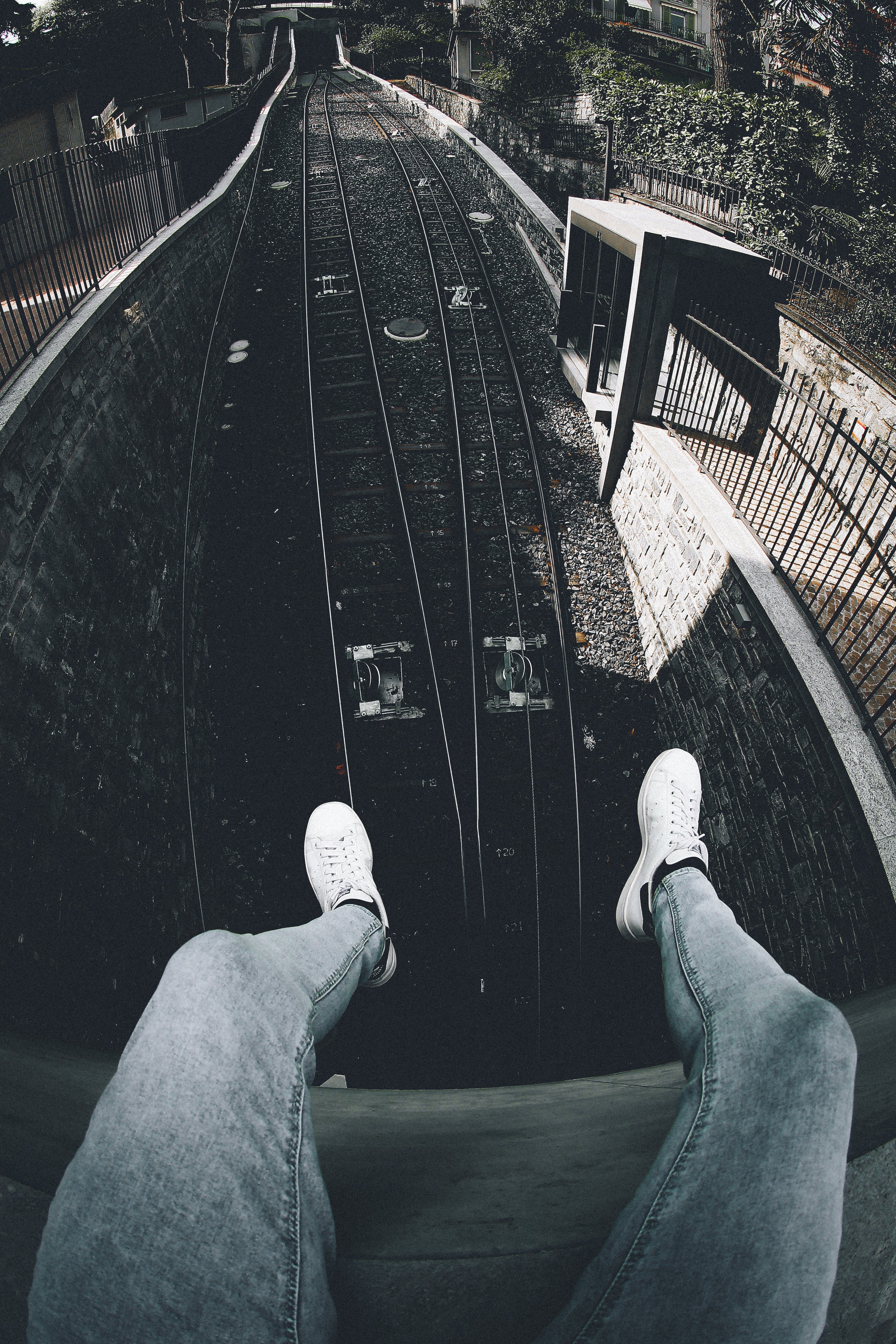 Person Siting on Roof in Front of Train Railway