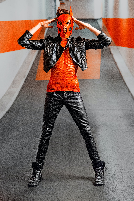 Man In Black Leather Jacket And Pants Wearing Orange Mask