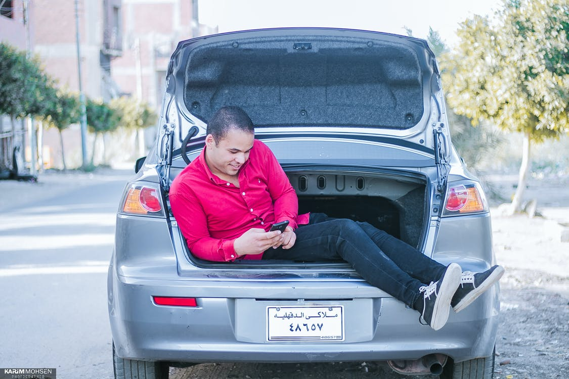 Man Seating on Car Trunk