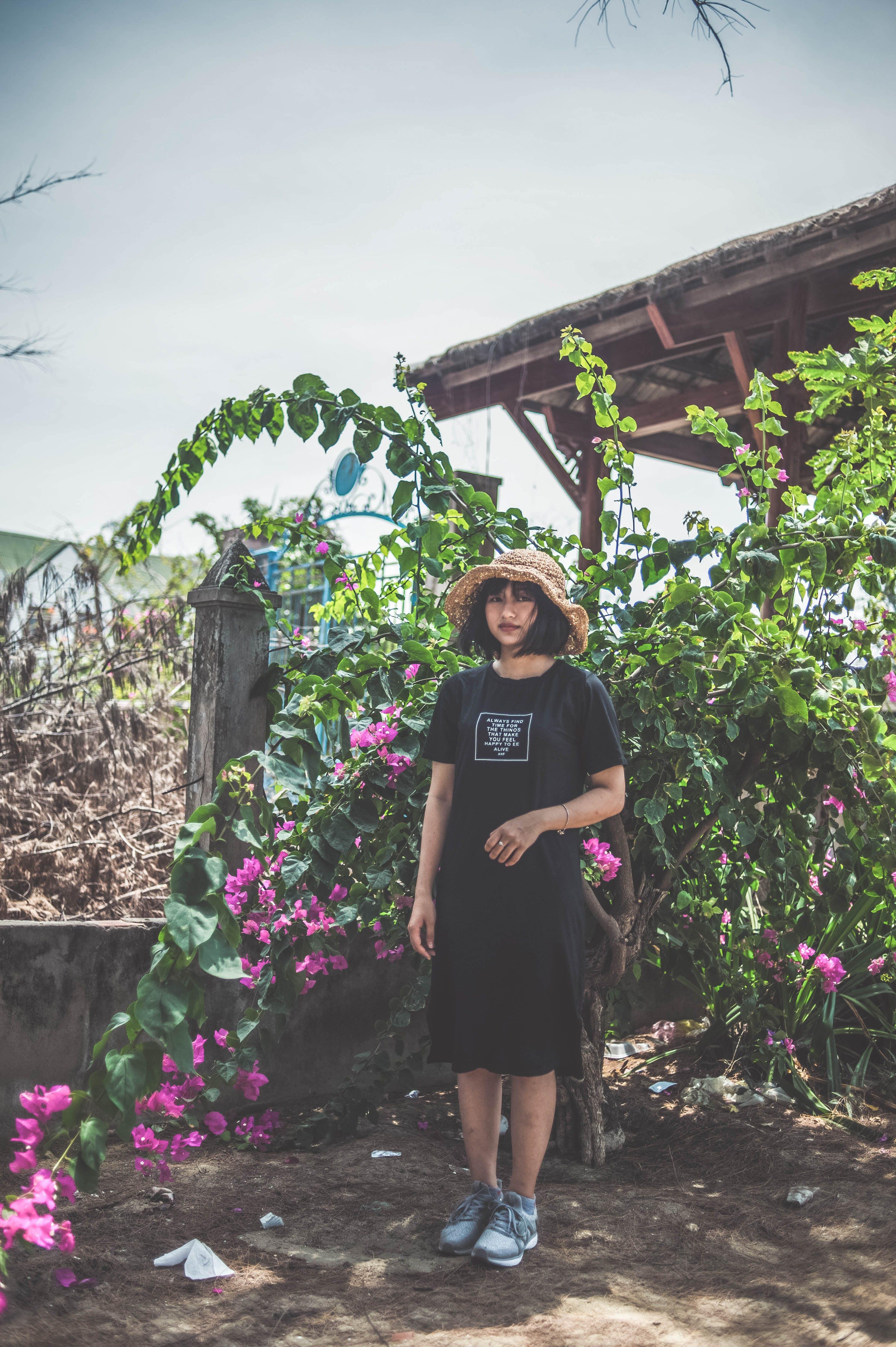 Woman Wearing Black Crew-neck Dress Standing Beside Pink Flowers