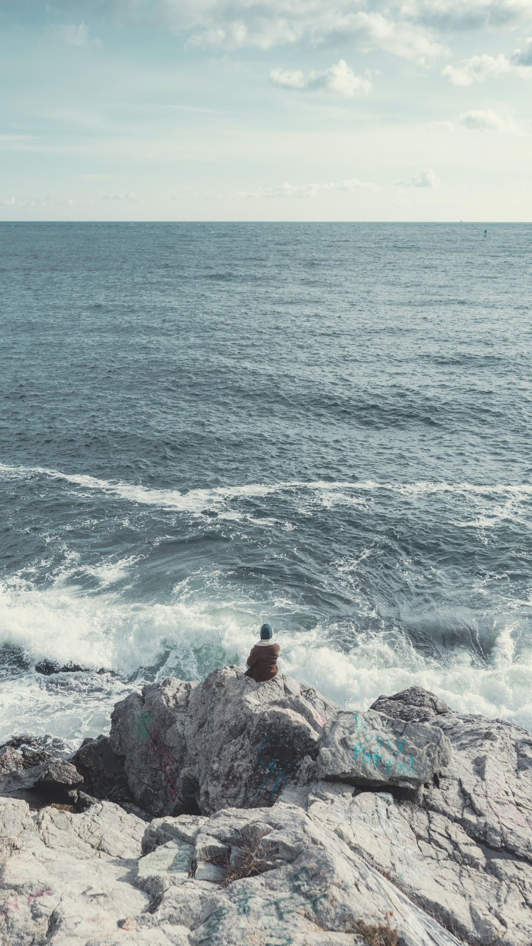 Person Sitting on Gray Rock Near Sea