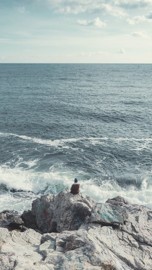 Person Sitting on Gray Rock Near Sea