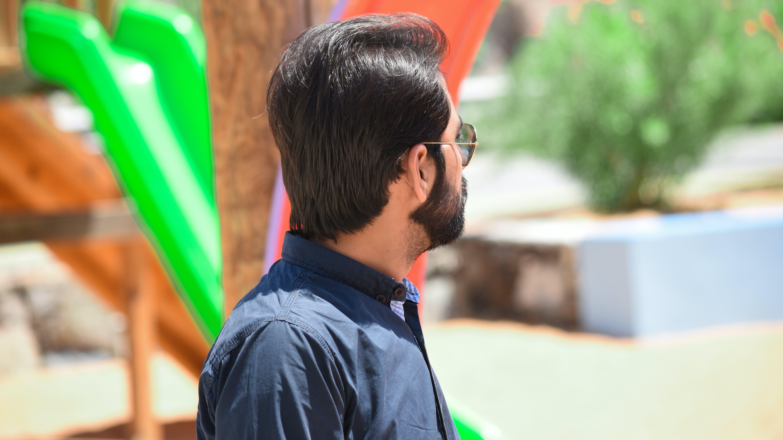 Man Wearing Black Button-up Shirt Standing Near Green and Brown Slide