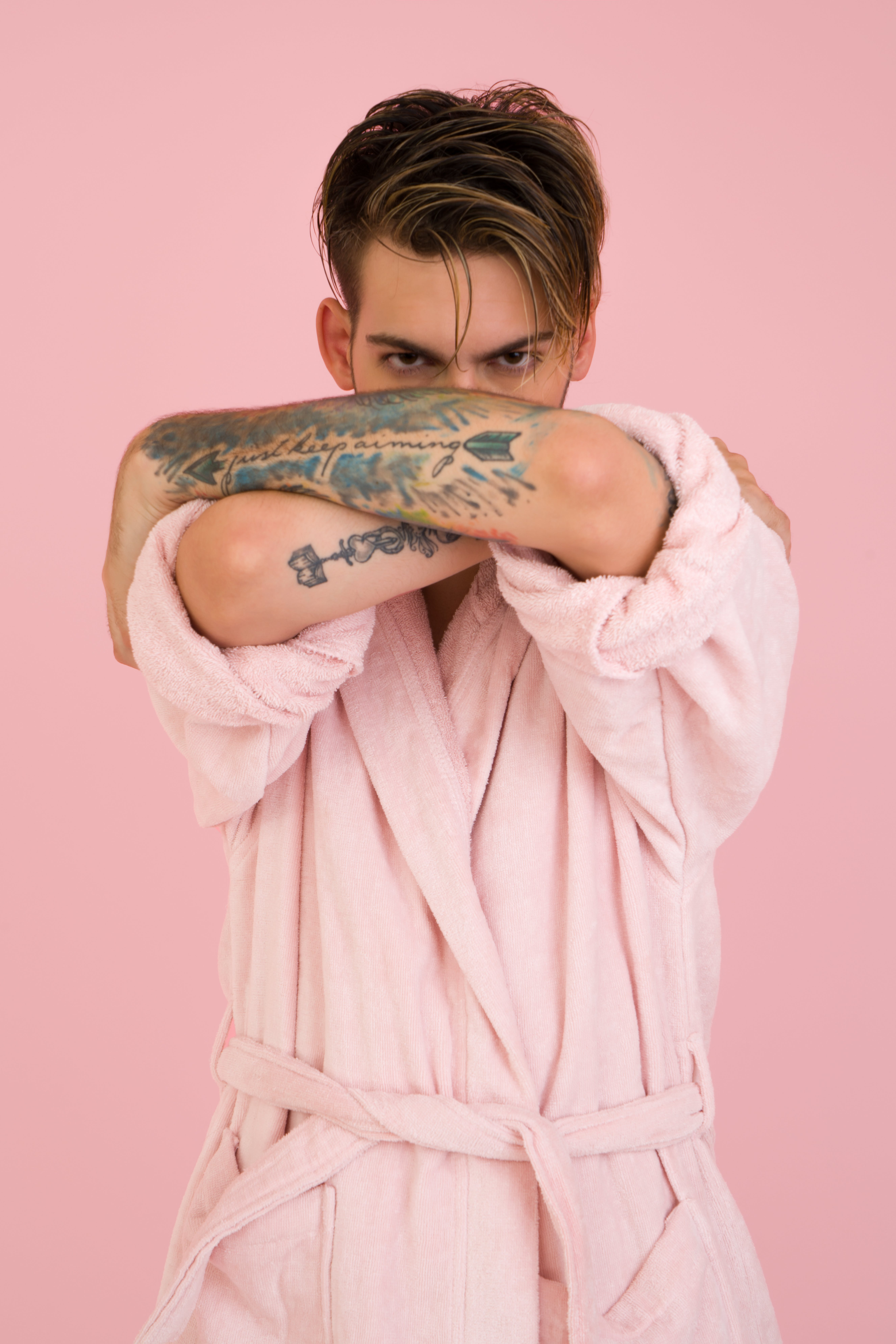 Man Wearing White Bathrobe Stands Near Pink Wall