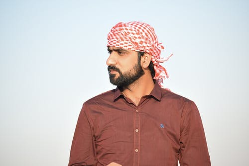 Portrait Photo of Man in Red Button-up Shirt and Red-and-white Headscarf