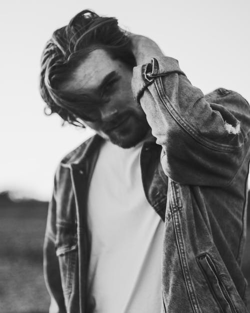 Grayscale Photo of Man Wearing Denim Jacket