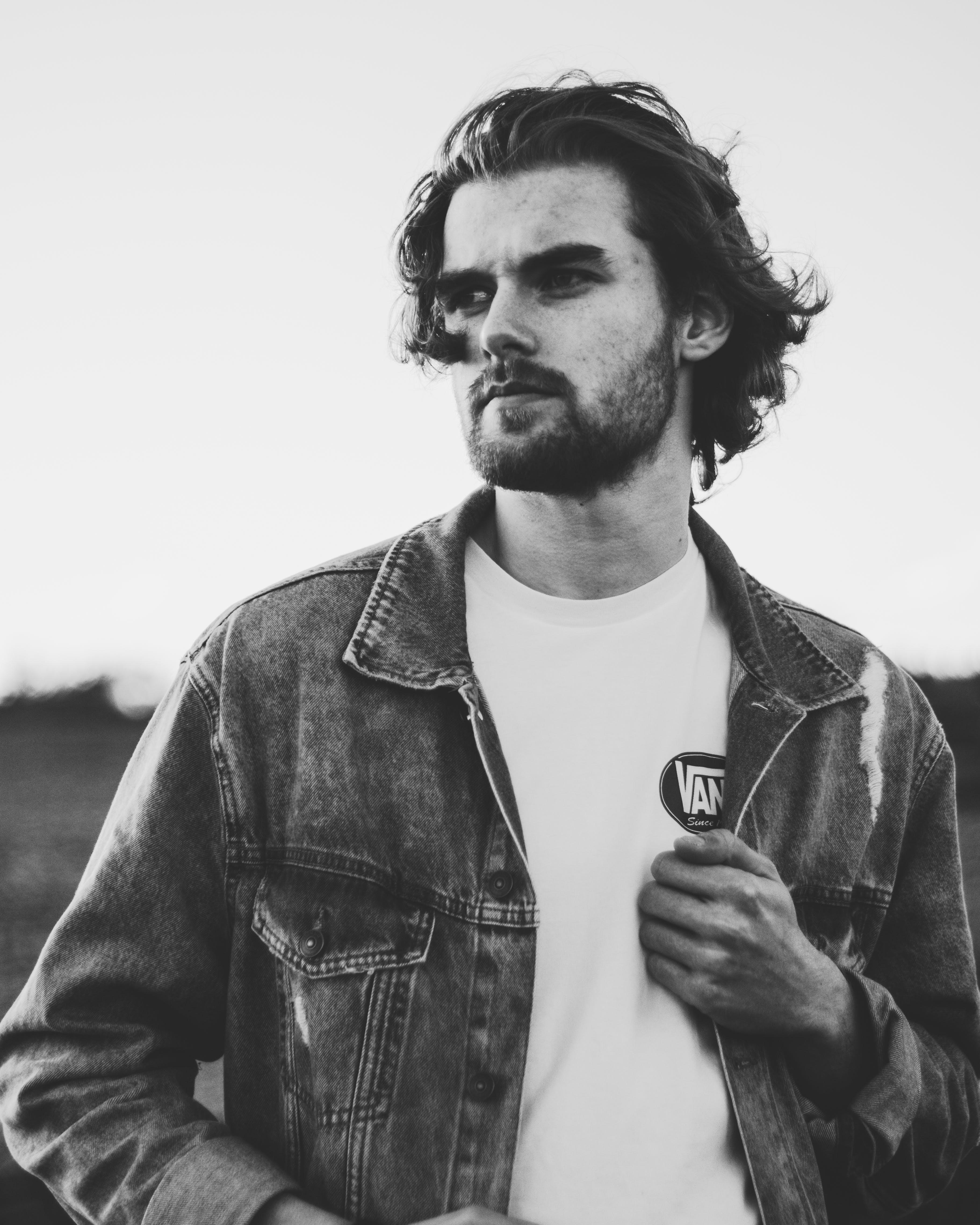 Grayscale Photo of Man Wearing Denim Jacket
